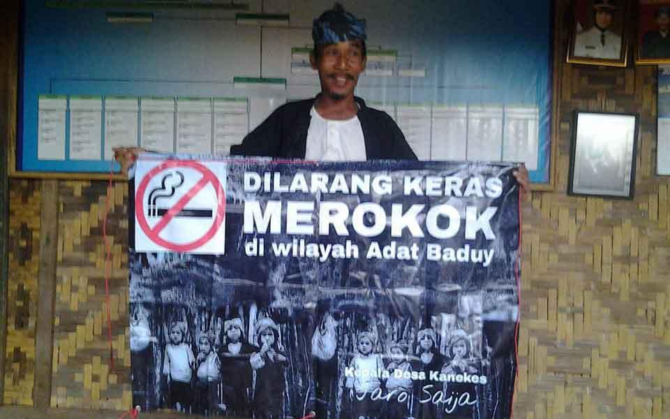 Orang Kanekes berpose dengan poster larangan merokok